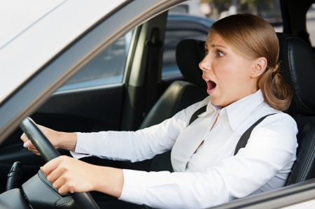 frightened young woman holding the steering wheel and shouting photo