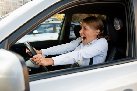 startled: frightened woman sitting in the car and holding for the wheel