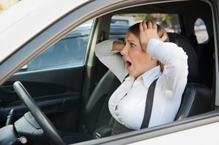 bange vrouw zitten in de auto en houdt haar hoofd Stockfoto