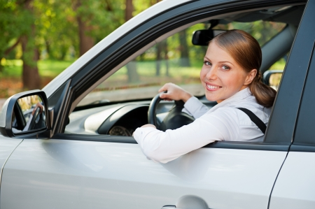 prosperous: alluring young woman driving the car and smiling Stock Photo