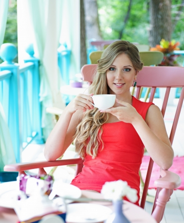 attractive young woman holding cup of tea and looking at camera  shot in the cafe photo