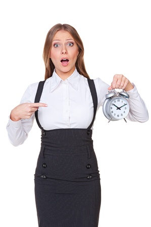 discontented: disturbed businesswoman pointing at the alarm clock. isolated on white background Stock Photo