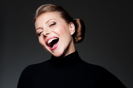 merriment: studio shot of happy young woman over dark background