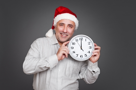 excited man with santa hat holding clock. studio shot over grey background photo
