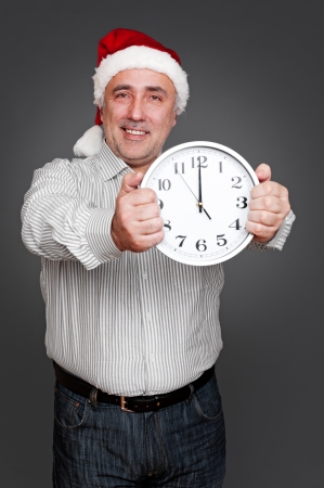 excited man in santa hat holding clock. studio shot over dark background photo