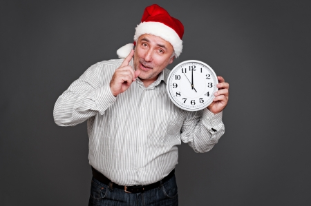 senior man in santa hat holding clock and showing the attention sign. studio shot over grey background photo