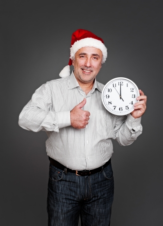 happy xmas man showing thumbs up and holding clock. studio shot over dark background photo