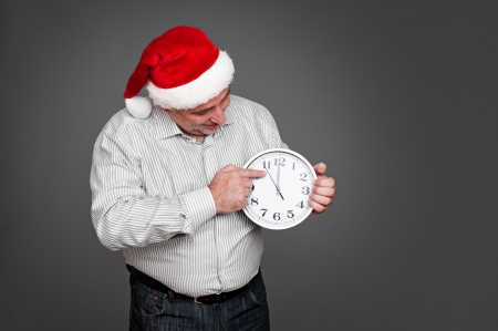 man in santa hat holding the clock and looking at the time. studio shot on grey background photo