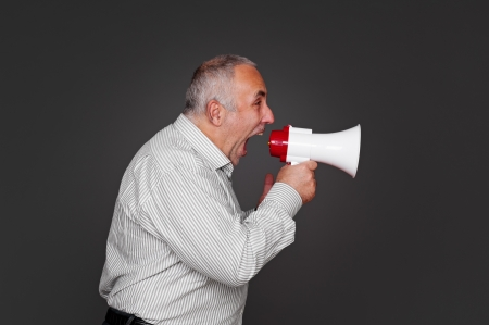 sideview of senior man shouting using megaphone over grey background Stock Photo - 16790341