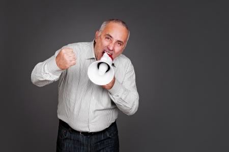 emotional senior man shouting with megaphone against grey background photo