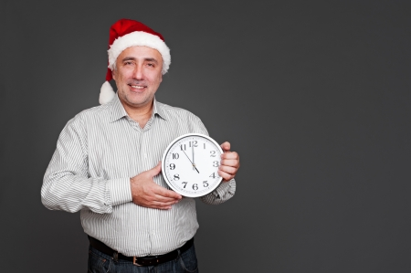 xmas man showing the clock and smiling. studio shot over dark background photo