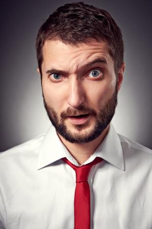 discredit: closeup portrait of amazed man over grey background