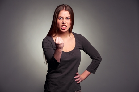angry face: angry woman threatening the fist over grey background