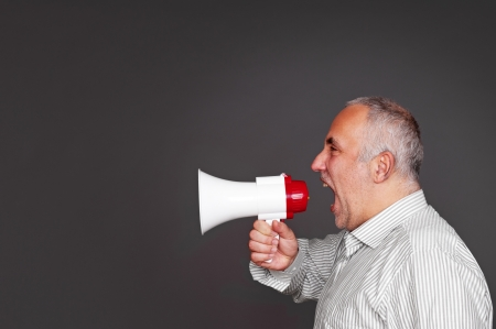 sideview of emotional boss with megaphone over dark background Stock Photo - 17376648