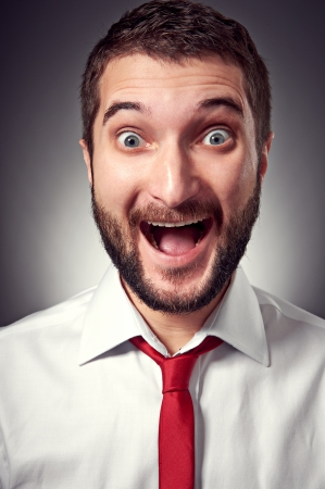caras emociones: Retrato de hombre joven emocionado con barba sobre fondo gris