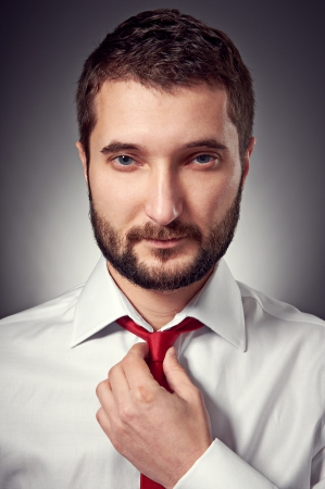 portrait of handsome man with beard over grey background photo