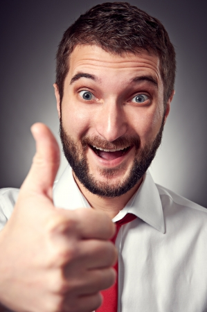 happy caucasian man showing thumbs up over grey background photo