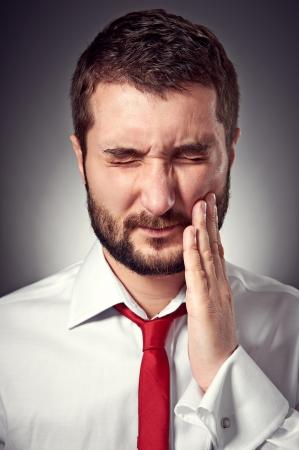 man have a toothache. studio shot over dark background photo