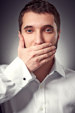 young adult man holding hand over his mouth over grey background photo