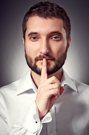 handsome man with beard showing silent sign. studio portrait over dark background Stock Photo - 17376653