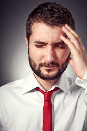 portrait of man with headache over grey background photo