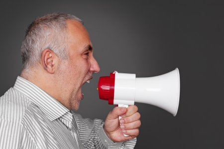 mature man with megaphone over grey background Stock Photo - 17376649