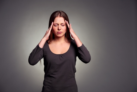 afflict: young sad woman have a headache. studio shot over grey background