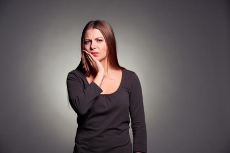bad teeth: sad woman have a toothache. studio shot over dark background