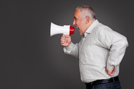 senior man shouting through the megaphone. studio shot over grey background photo