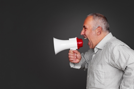 sideview of senior man with megaphone over grey background photo