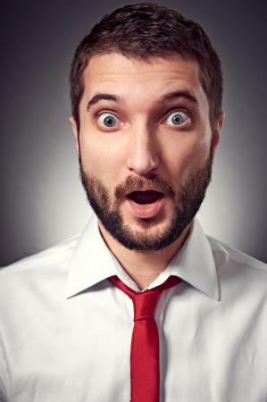 discredit: emotional portrait of surprised man over grey background