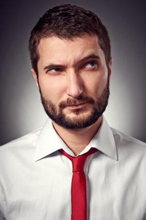 discredit: thoughtful man with distrust looking up over grey background Stock Photo