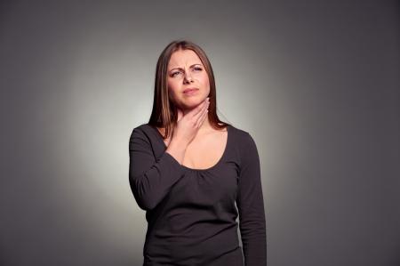 angina: infeliz mujer tiene un dolor de garganta. tiro del estudio sobre fondo oscuro Foto de archivo