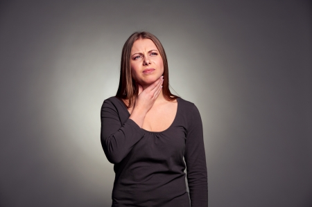afflict: unhappy woman have a throat pain. studio shot over dark background