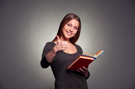 attractive young woman holding the books and showing thumbs up over dark background photo