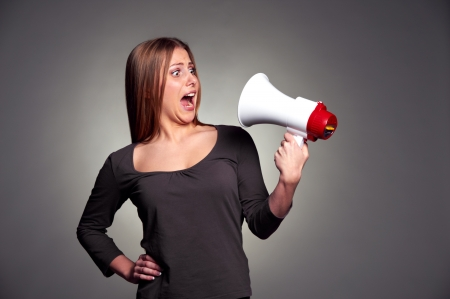fear face: frightened woman looking on megaphone. studio shot over dark background