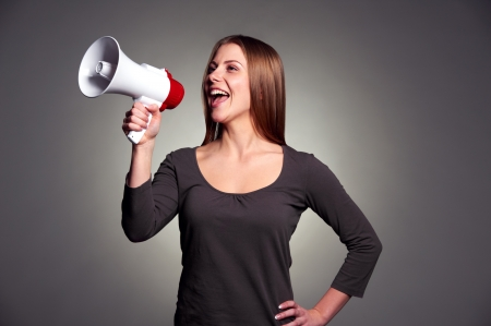 happy woman with loudspeaker over dark background Stock Photo - 17424899