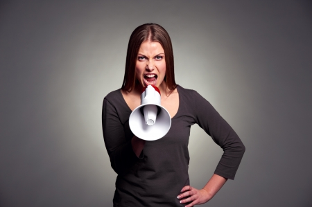 severe woman with megaphone. studio shot over dark background photo