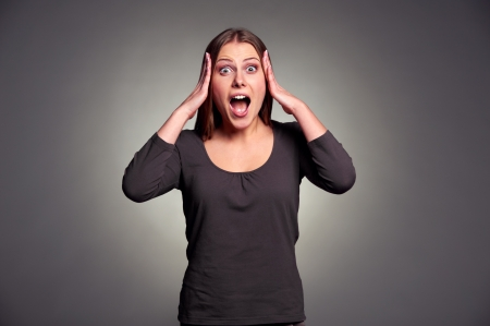 startled: studio shot of shocked young woman over dark background