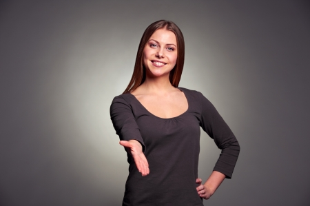 friendly young woman extending her hand for the handshake. studio shot over dark background photo