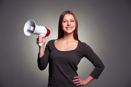 friendly young woman holding megaphone and smiling. studio shot over dark background Stock Photo - 17424921