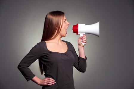 attractive young woman holding megaphone over dark background Stock Photo - 17424900