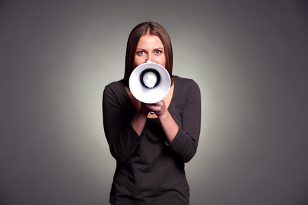 young woman holding loudspeaker. studio shot over dark background photo