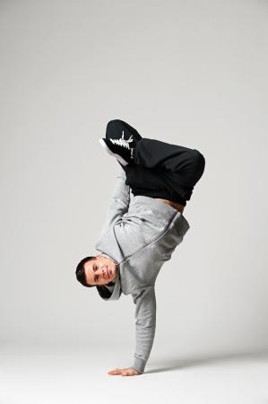 full length portrait of cool dancer over grey background