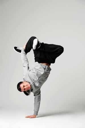 full length portrait of hip-hop dancer over grey background