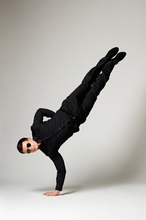 hand movements: stylish man in black formal wear and sunglasses standing on one hand. studio shot over grey background