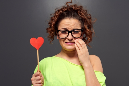 the sad girl: young woman in glasses with broken heart