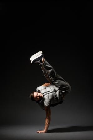cool break dancer standing on the freeze over dark background