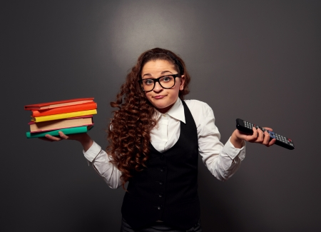 funny woman in glasses with pile of books and tv remote. picture over dark background photo