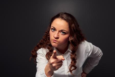 nespokojen: studio shot rozzlobený žena ukazuje na kameru. Obrázek přes tmavé pozadí